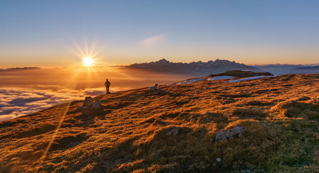 Hiker and a dog at the top of the mountain at sunset with aeautiful view of Julian Alps.