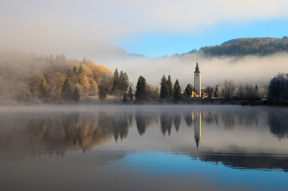 The beautiful Lake Bohinj in the morning with the medieval Church of St. John the Baptist