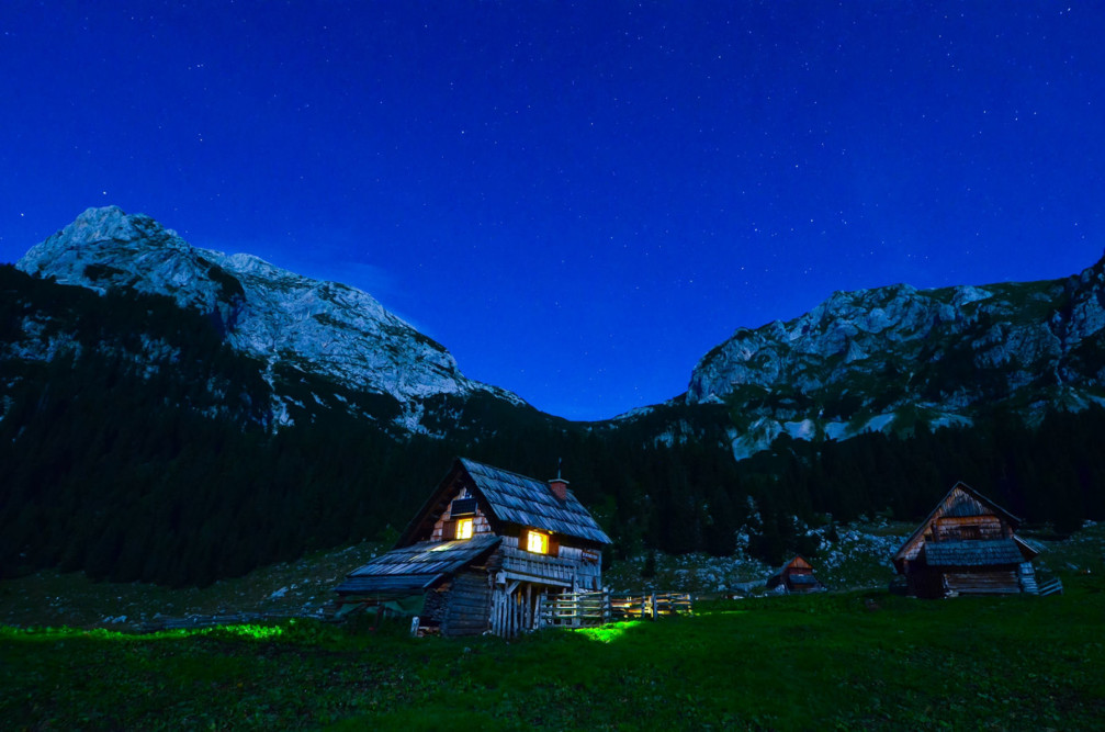 Laz Alpine pasture a.k.a. Planina v Lazu at night with wooden barns and farmhouses in traditional style