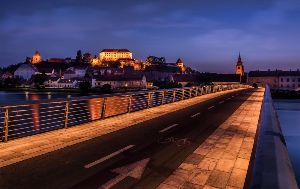 Night view of the town of Ptuj with pedestrian bridge across the Drava river, Slovenia