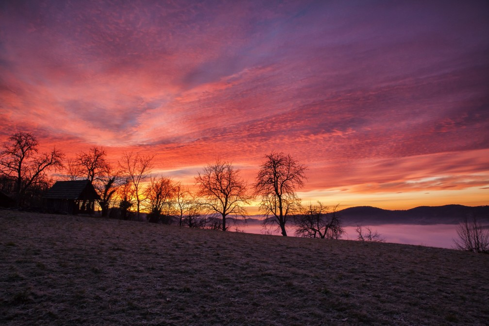 Breathtaking winter sunset with vivid colors of red and orange through purple near Dolgo Brdo, Slovenia