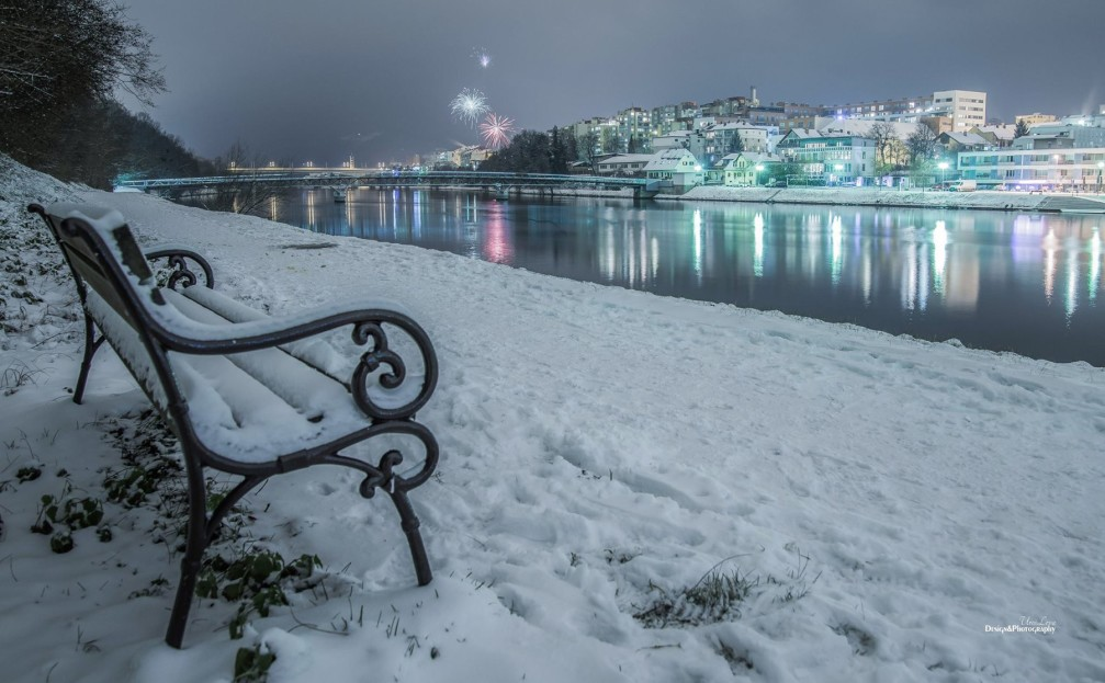 Path and one of many benches along the Drava river in winter in Maribor, Slovenia