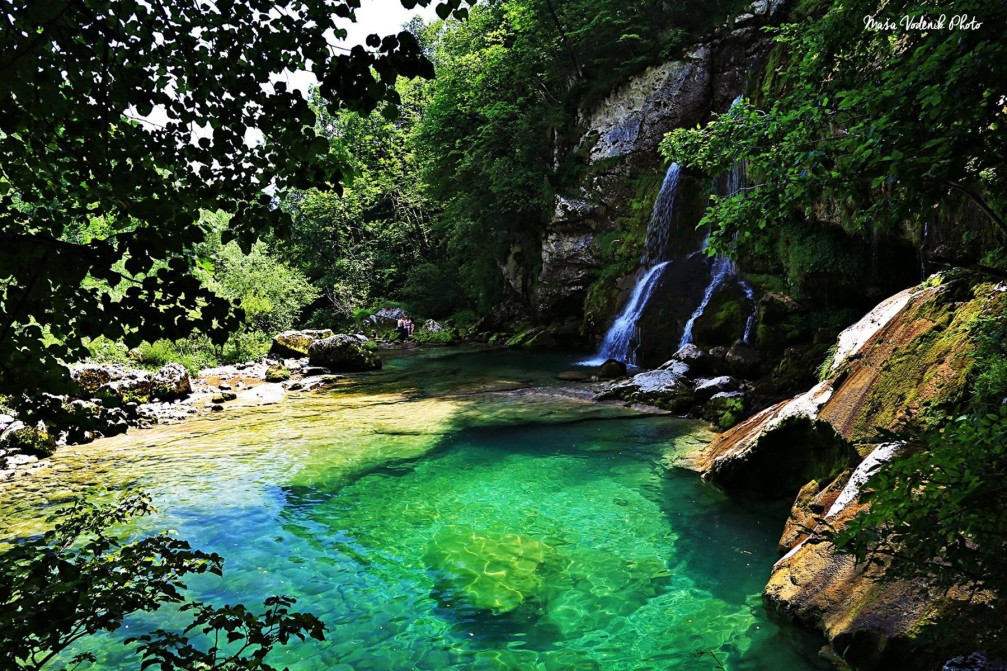 Virje waterfall set in a pretty glade and the emerald green pools below it are gorgeous
