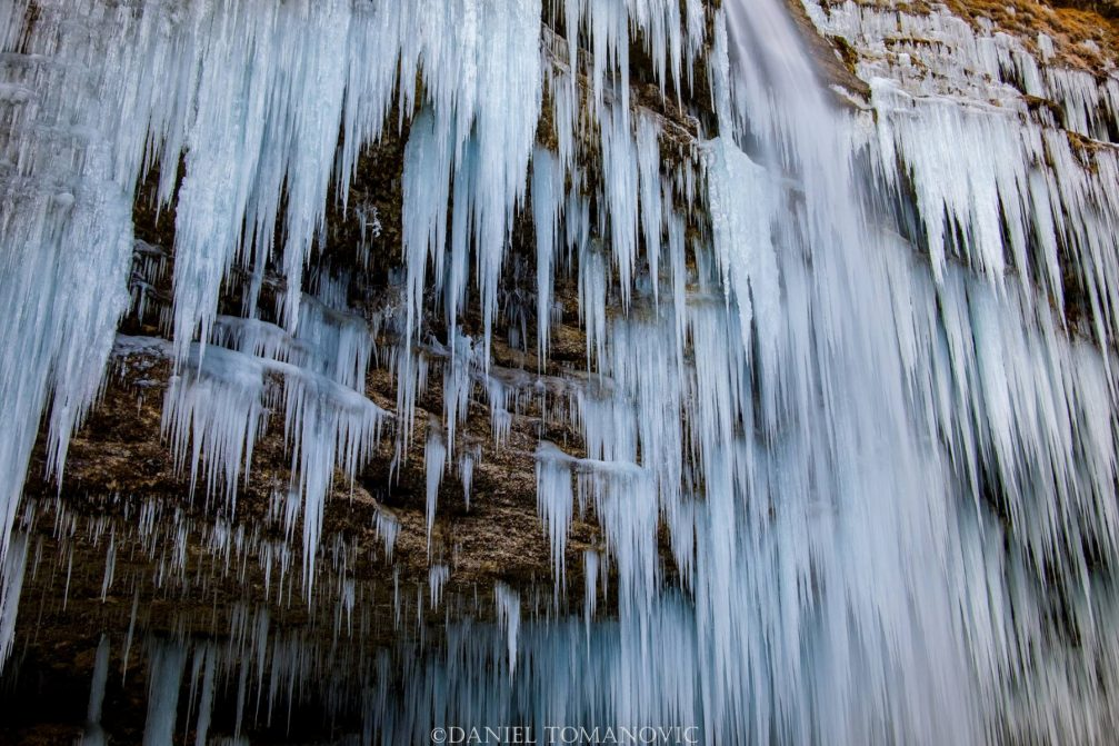 Frozen Pericnik Falls with a giant wall of icicles during the winter season