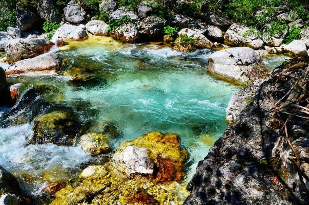 The crystal-clear emerald-green Soca river near its source in the Trenta valley