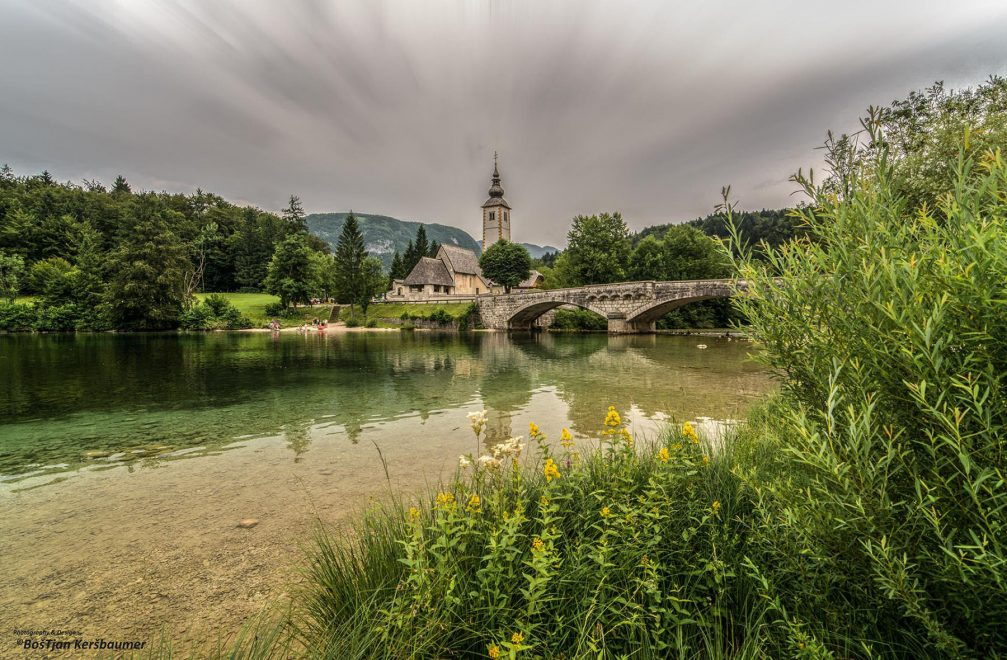 Lake Bohinj with a bridge and the Church of St John the Baptist in the background