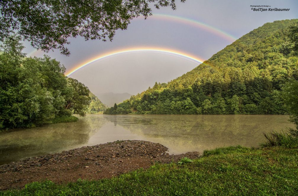 A colorful double rainbow across the Drava river near the Ozbalt village in Slovenia