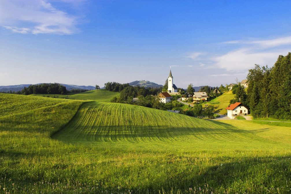The village of Zavratec with the Church of St. Ulrich in the hills of western Slovenia