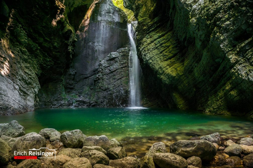 View of the beautiful Kozjak waterfall with a vast emerald green pool at its base