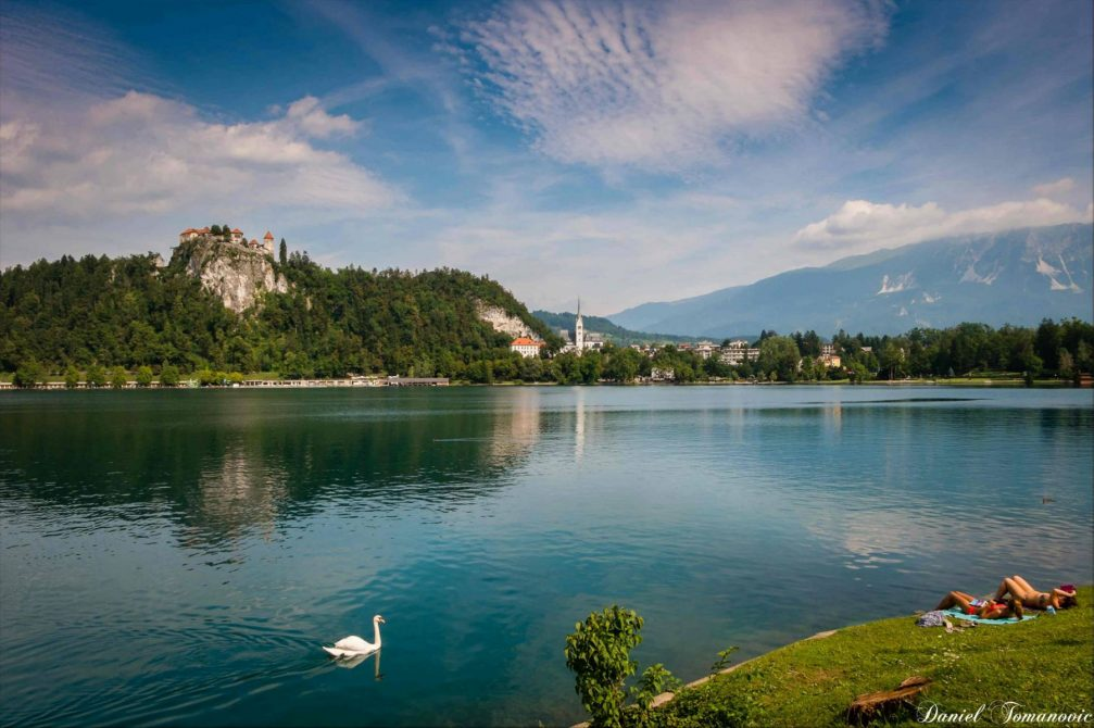 Lake Bled with its cliff-top castle and a few people sunbathing on the shore