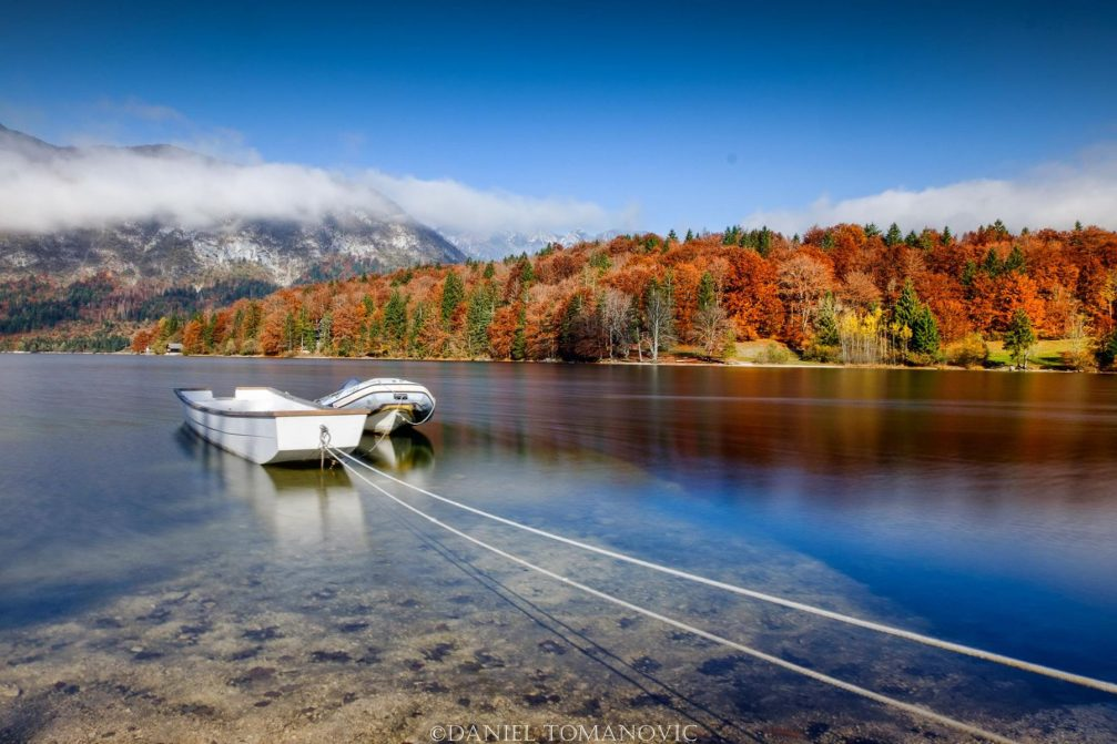 Boats docked at Lake Bohinj in Slovenia on a sunny autumn day