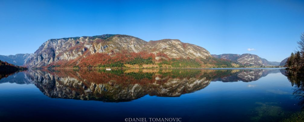 Lake Bohinj panorama in autumn with colorful foliage and water reflection