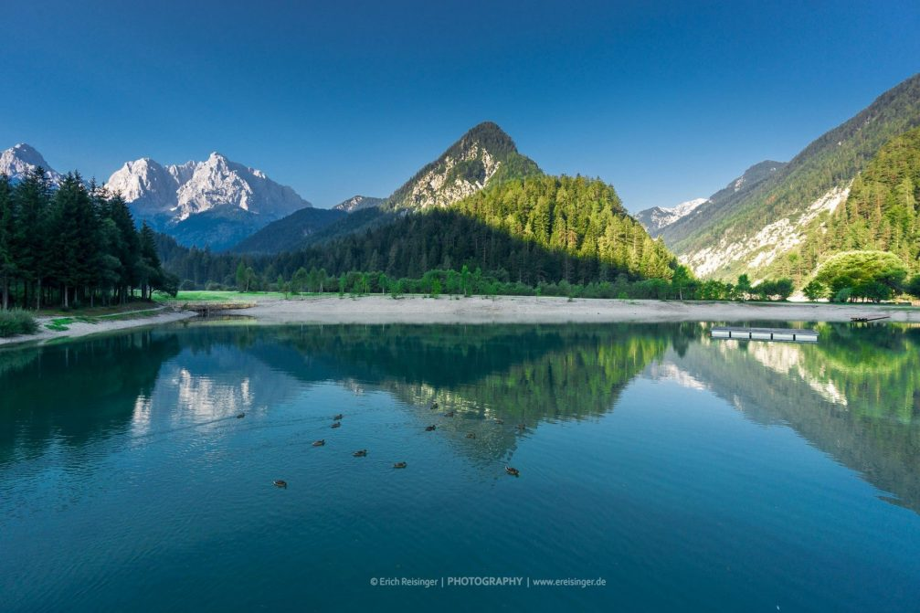 The picturesque Jasna lake surrounded by the high mountain peaks of the Julian Alps