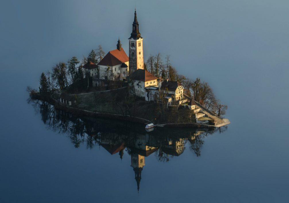 An elevated view of Bled Island with a Gothic church on it in snowless winter time