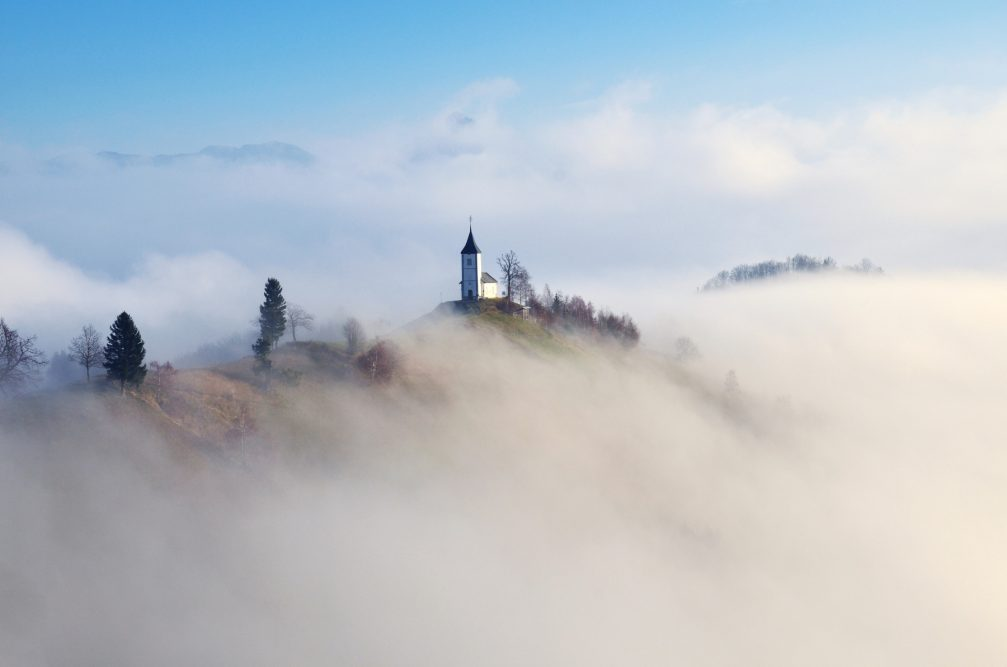 Jamnik church on a misty morning, perched on a hill on the Jelovica Plateau, Slovenia