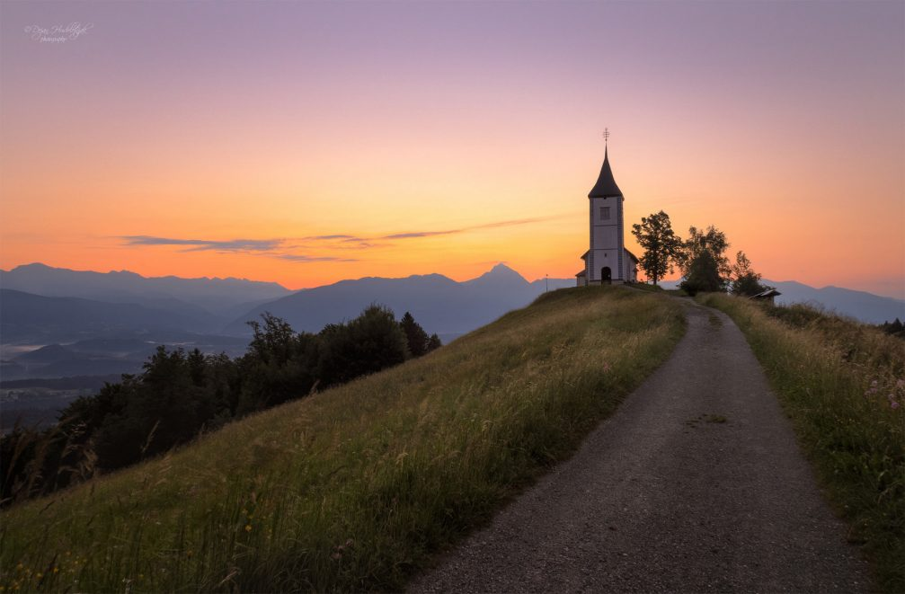 A dirt road leading to the Church of Saints Primus and Felician in Jamnik, Slovenia