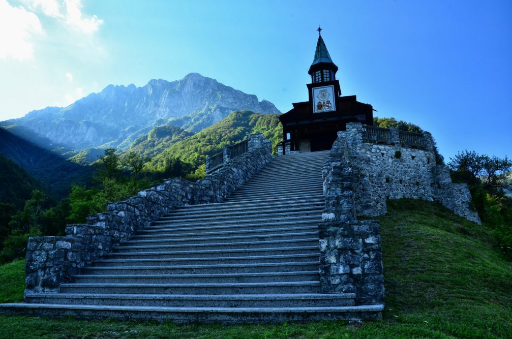 The Javorca Memorial Church of the Holy Spirit with the Julian Alps in the background