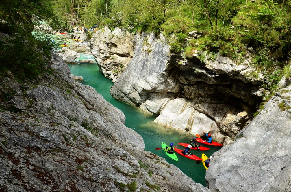 A group of water-sports enthusiasts kayaking on the Soca River in Slovenia
