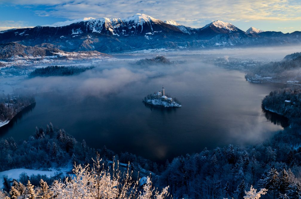 An elevated view of Lake Bled in winter with fresh snow all around
