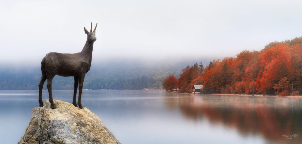 Statue of Goldhorn chamois or Zlatorog with Lake Bohinj in the background