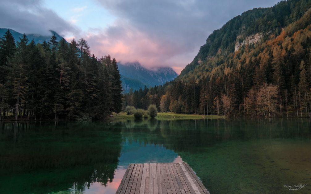 Lake Plansarsko Jezero, emerald green and surrounded by meadows and majestic mountains in Jezersko, Slovenia