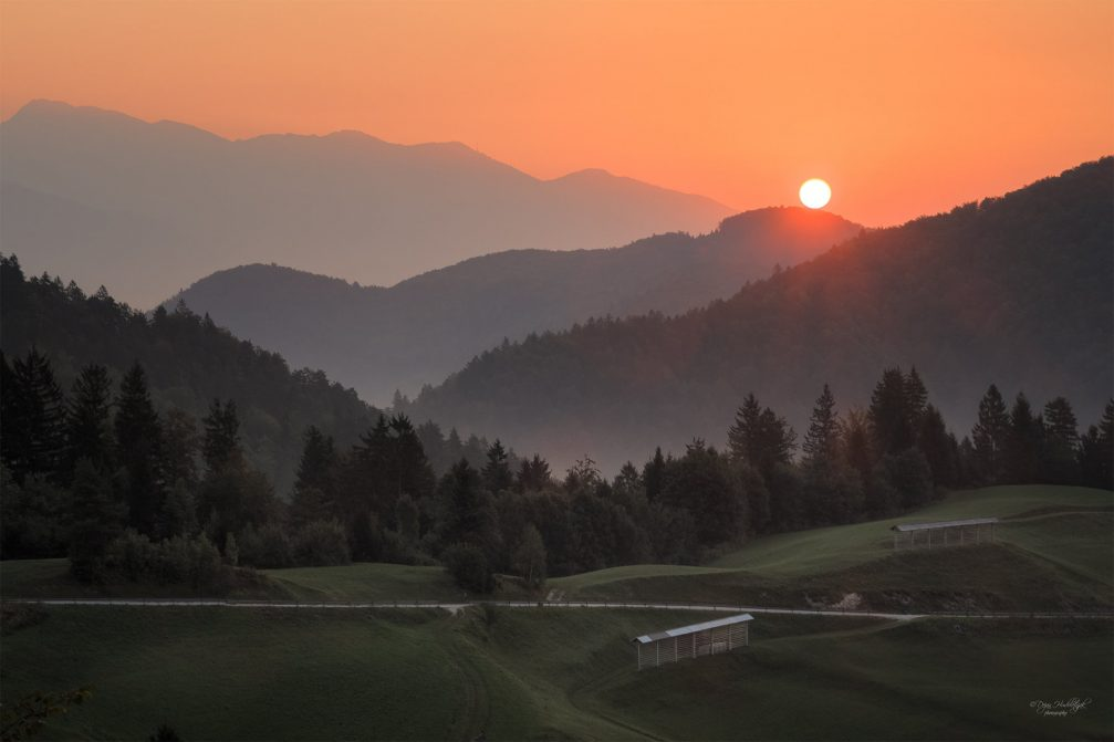 A beautiful sunset over the serene countryside of Nemilje in northwestern Slovenia