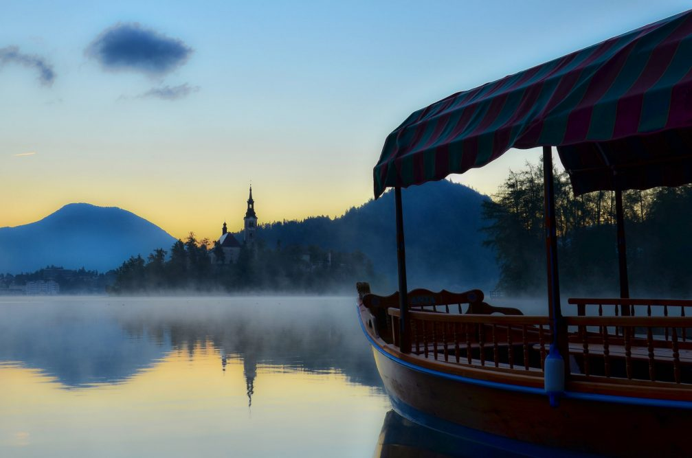 The traditional Pletna boat in Lake Bled with Bled Island in the background