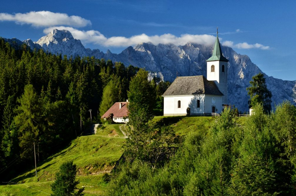 Church of the Holy Spirit in Podolseva, Slovenia with the Kamnik-Savinja Alps in the background