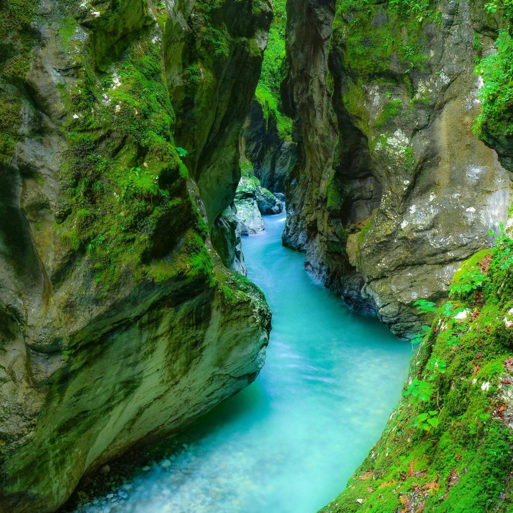 Crystal clear turquoise water softly flowing through the canyon walls of the Tolmin Gorge in Slovenia