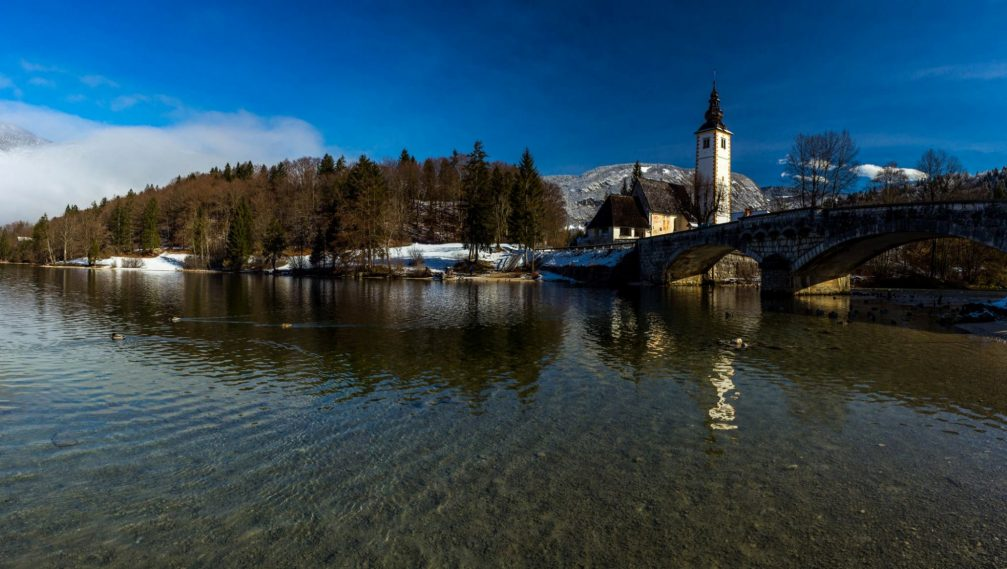 Lake Bohinj with a stone bridge and the church of St John the Baptist