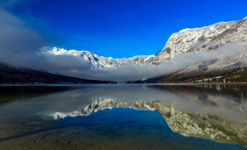 Lake Bohinj in Triglav National Park, Slovenia with snow-capped mountains on all sides
