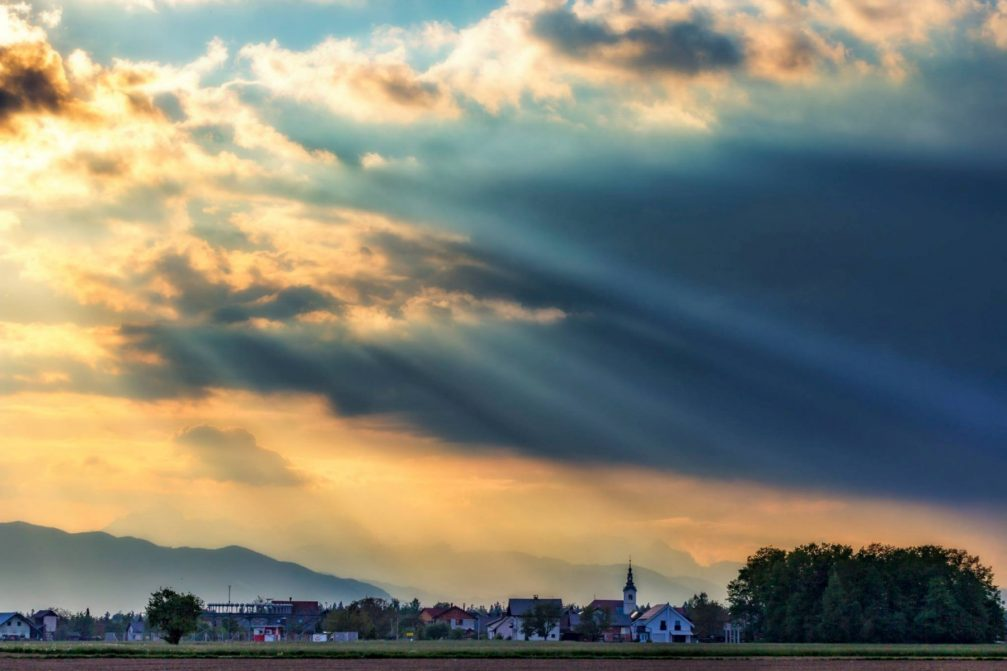Sun rays shining through clouds in Sencur, a small town in northwestern Slovenia