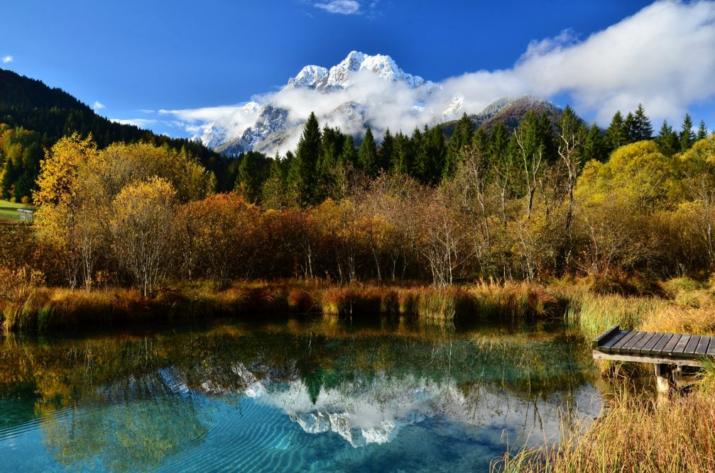 Zelenci Nature Reserve in autumn with Julian Alps in the background