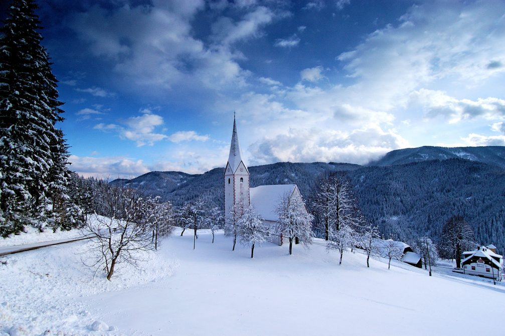 A church covered in snow in the winter in the countryside of the Koroska region of Slovenia