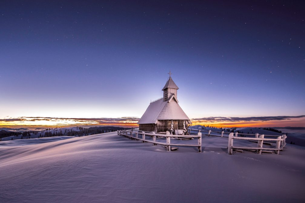 The tiny wooden Church of Our Lady of the Snows in Velika Planina covered with snow in the winter time