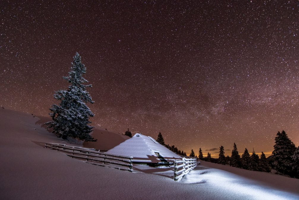 A unique, shingle-roofed wooden hut at Velika Planina at night covered with snow in the winter
