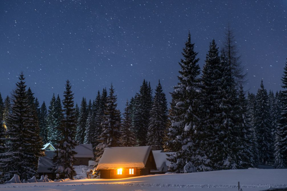 A group of Wooden huts covered with a thick layer of fresh snow at night at the Pokljuka Plateau in Slovenia