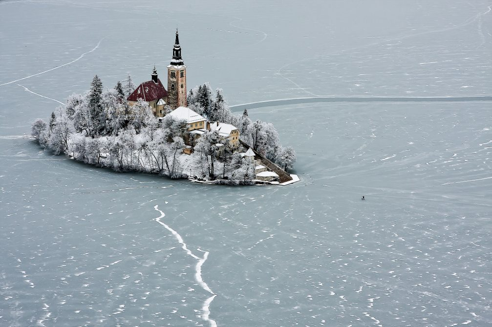 Frozen Lake Bled in the winter time with people walking on the ice to the island with a church