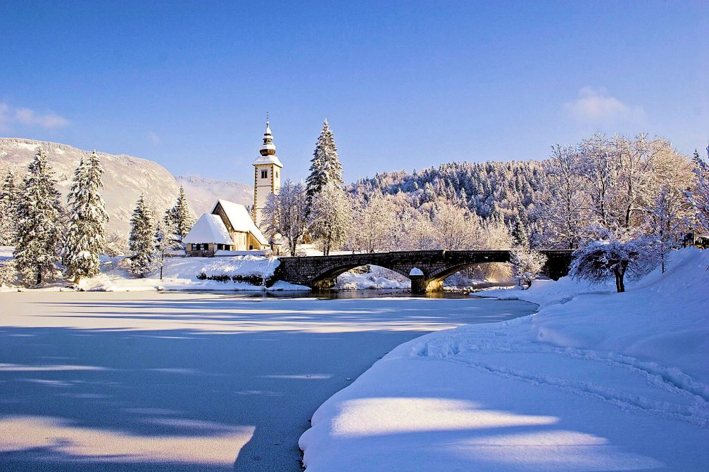 Frozen Lake Bohinj in the winter time with a church and stone bridge in the background
