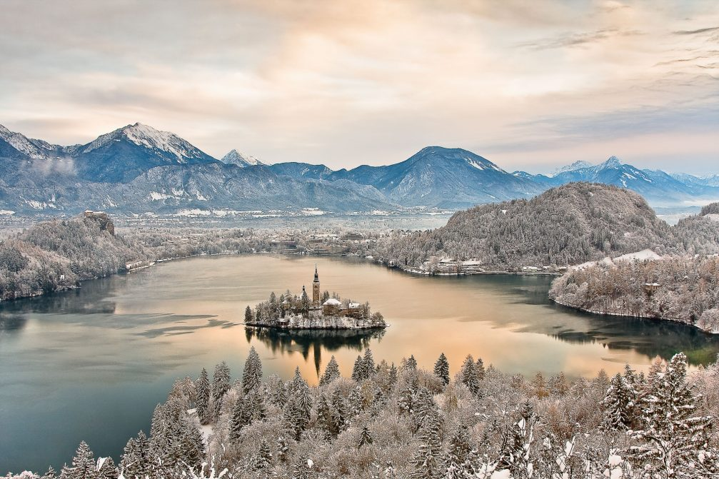 An elevated view of Lake Bled in the winter time with a cover of snow
