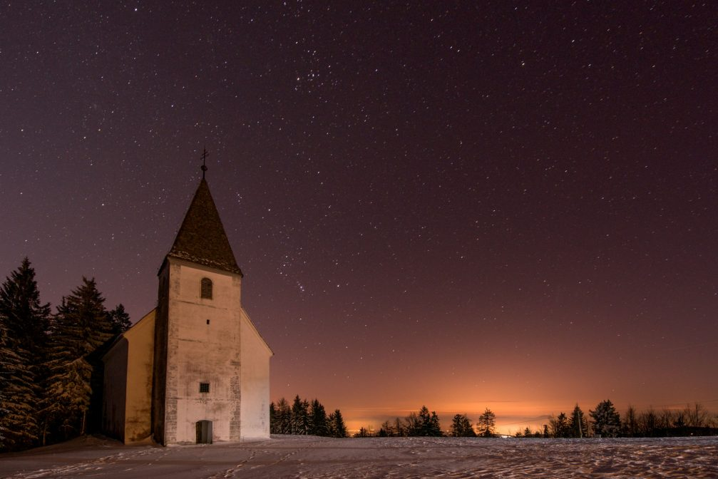 The exterior of the Church of St. Areh in the Pohorje Mountains at night in the winter