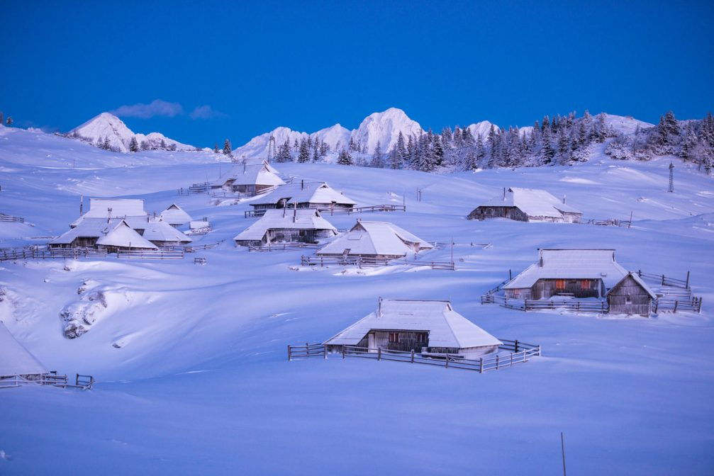 Shingle-roofed herdsmen's huts on the Velika Planina plateau covered with snow in the winter time